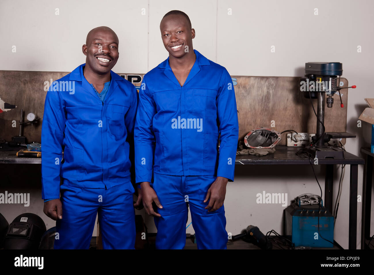 Two African mechanics standing in a workshop smiling at the camera - Stock Image