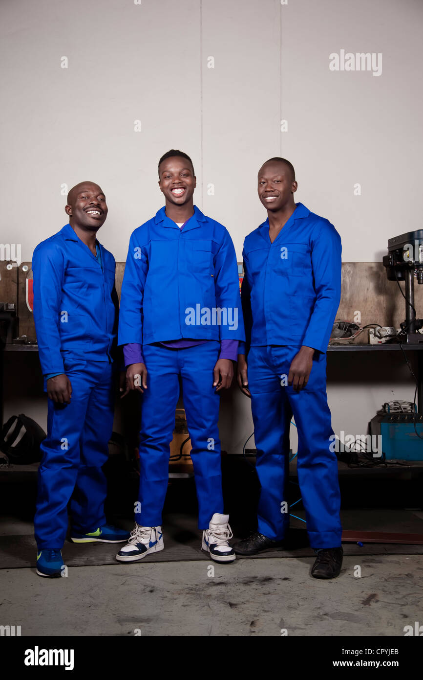 Three African mechanics standing in a workshop smiling at the camera - Stock Image