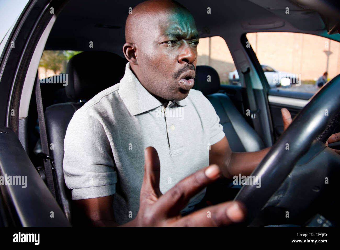 African Man Sitting In His Car Frustrated With It Not Starting