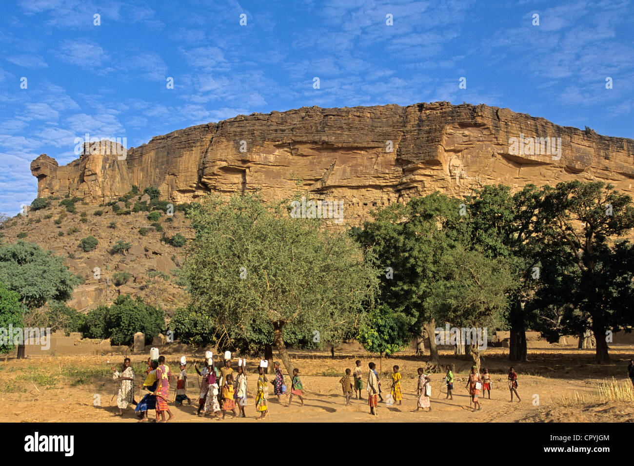 Mali Dogon Country Ennde water chore after school up to village's well bottom of Bandiagara falls listed as - Stock Image