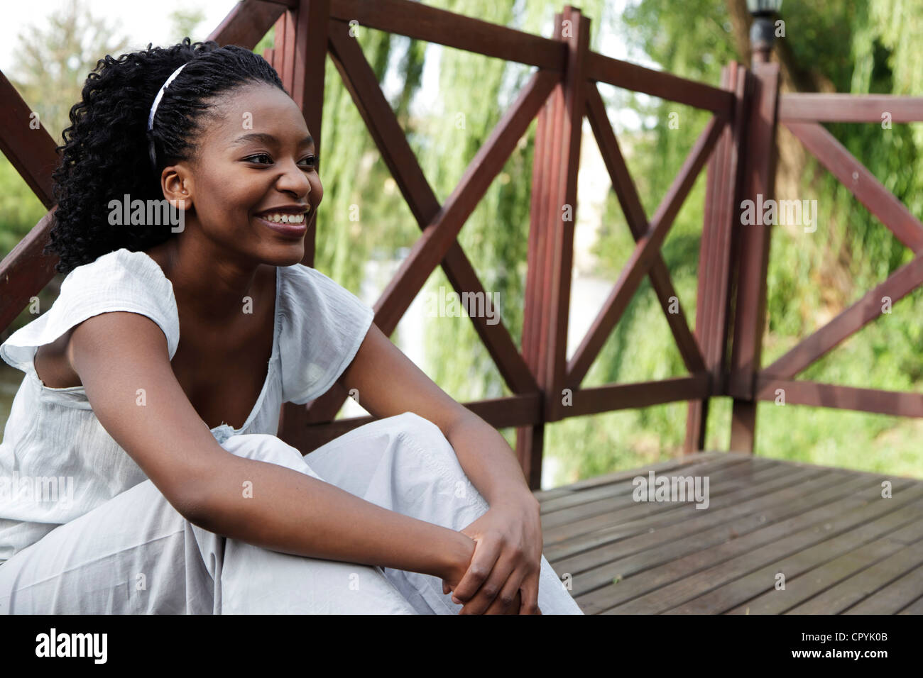 Young African woman sits on a wooden deck Stock Photo