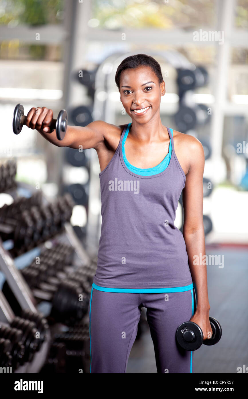 Young black female lifts weights in a gym - Stock Image