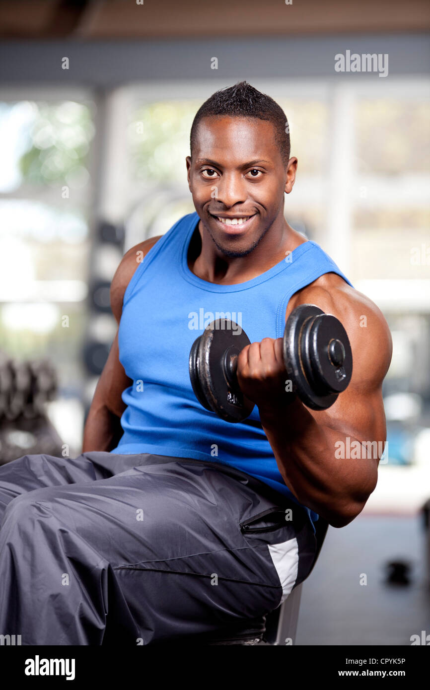 Young muscular black man lifting weights in a gym