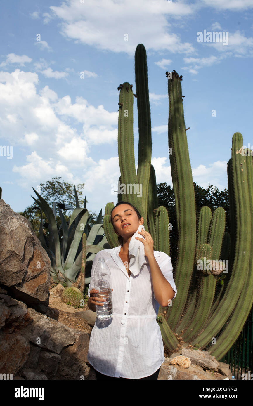 Heat wave, woman drying sweat in front of a cactus, Barcelona, Spain, Europe Stock Photo