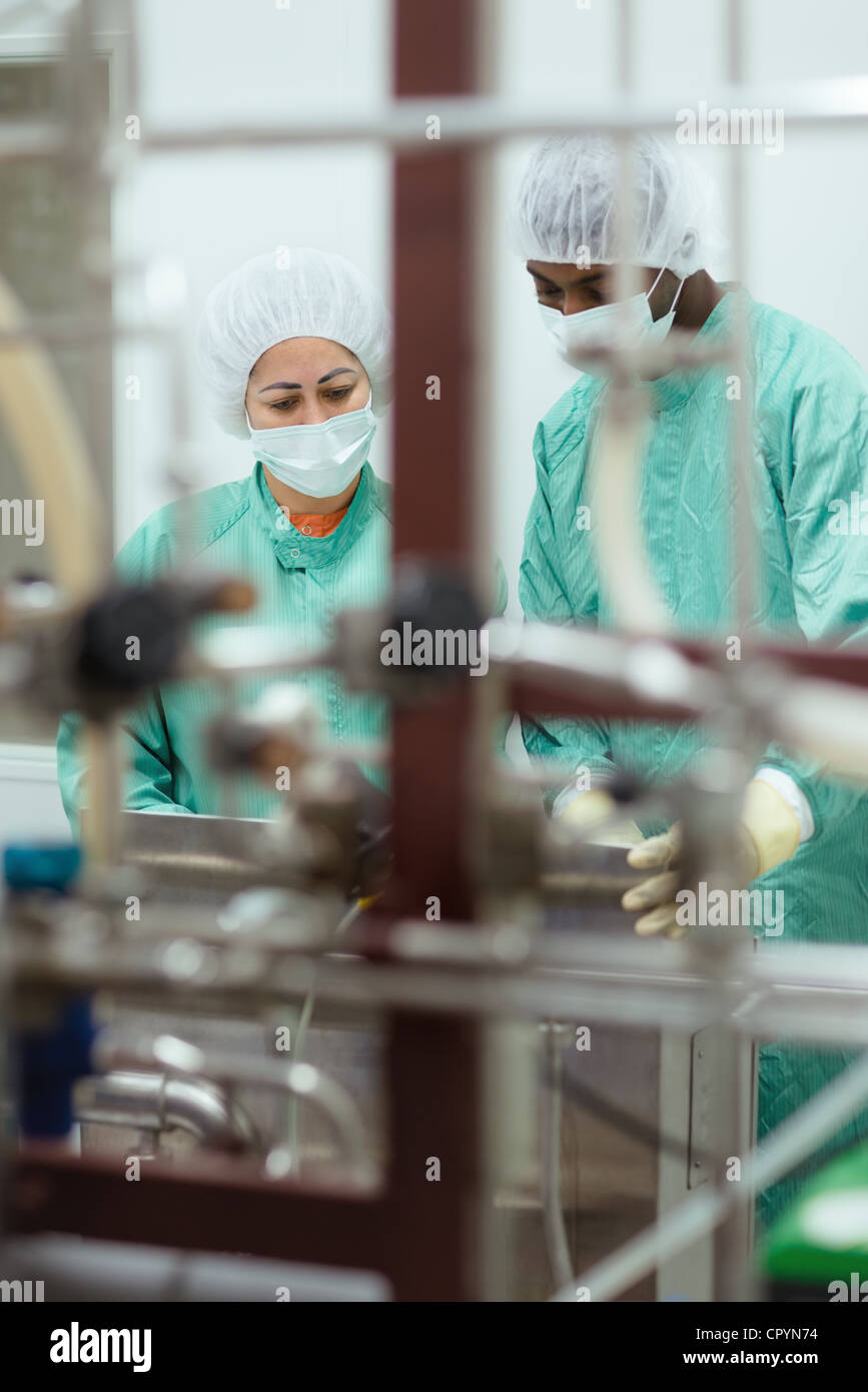 Laboratory technicians at work in medical plant with machinery and computers - Stock Image