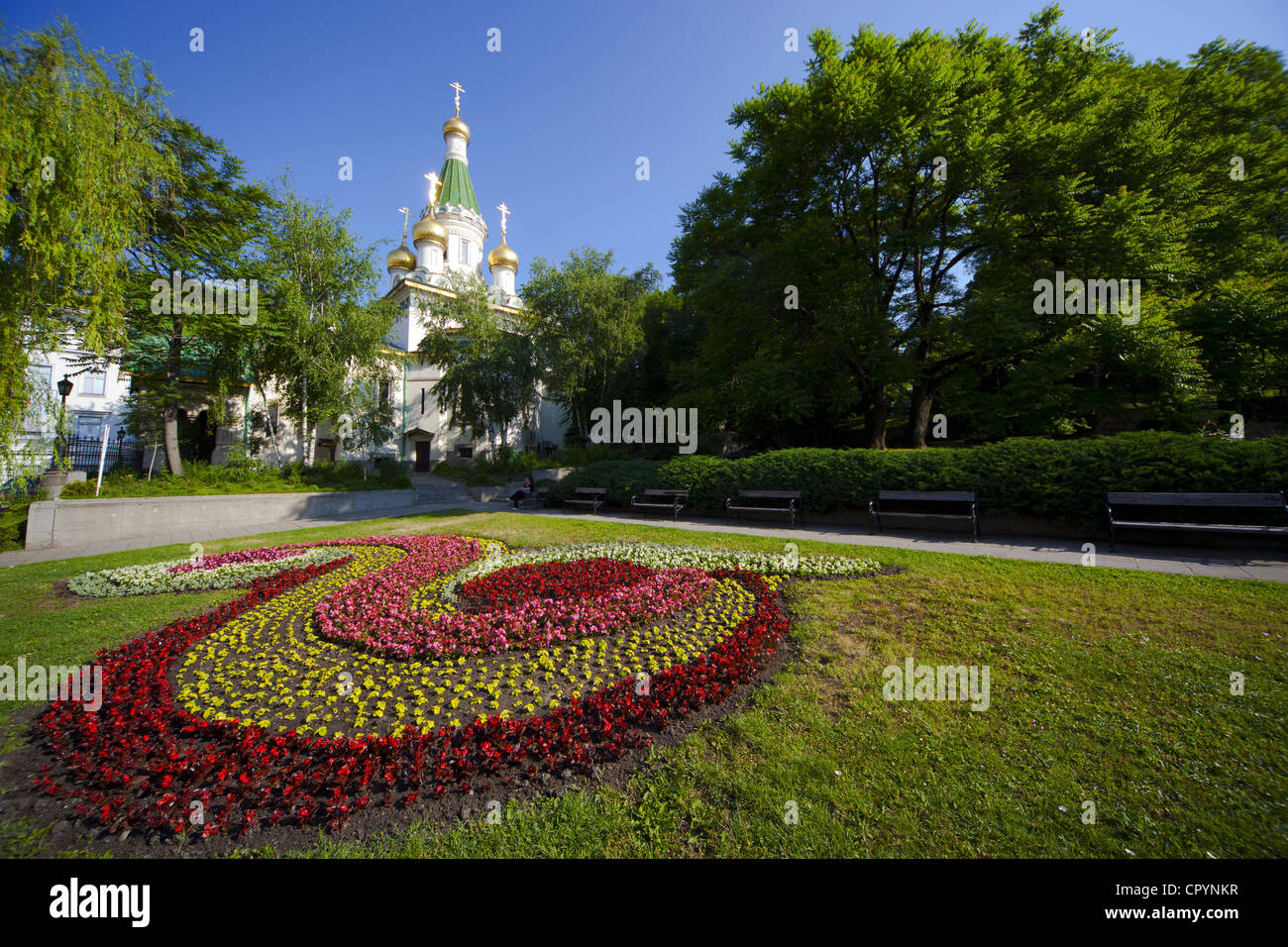 Flower bed in gardens with Church of St. Nicholas the Miracle Maker, behind, Boulevard Tsar Osvoboditel, Sofia, - Stock Image