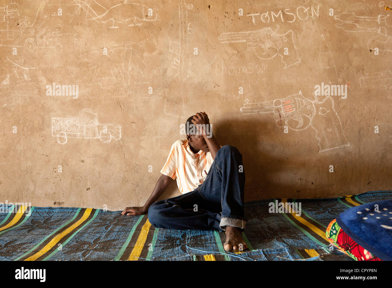 A former child soldier sits against a wall covered in drawings of firearms and military vehicles in a transit and - Stock Image