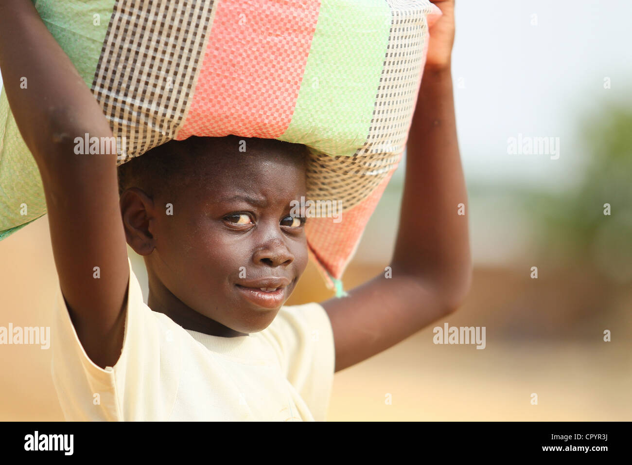 A girl carries a load on top of her head in N'Djamena, Chad on Thursday June 10, 2010. - Stock Image