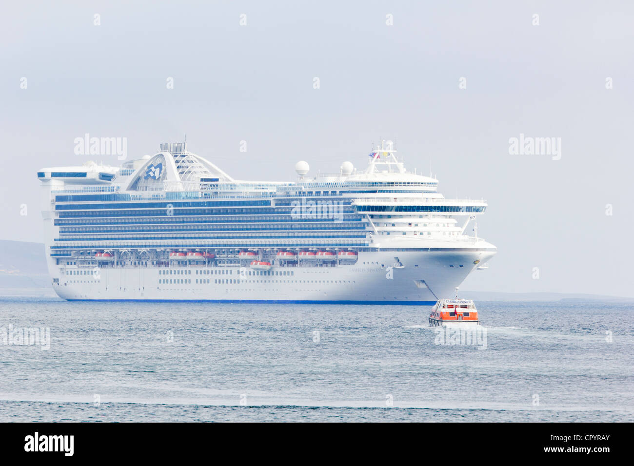 Kirkwall Harbour, Orkney Islands with Caribbean Princess anchored off shore - Stock Image
