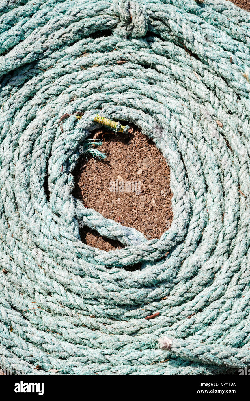 A coil of old green rope laid out on concrete. - Stock Image