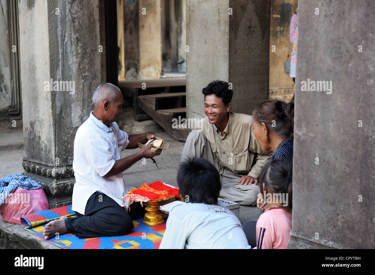 SIEM REAP, CAMBODIA - AUGUST 14: A group of local residents cast fortune on August 14, 2011 in Angkor wat temple, - Stock Image