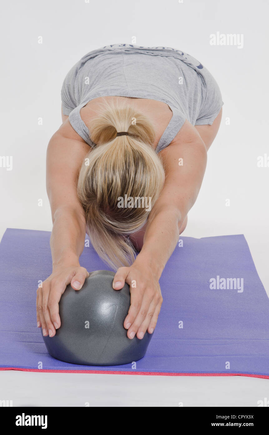 Young woman stretching on an exercise mat with an exercise ball - Stock Image