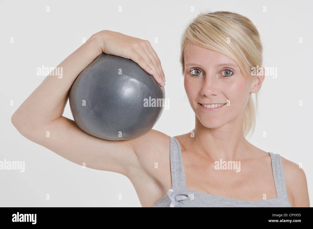Young woman holding an exercise ball - Stock Image