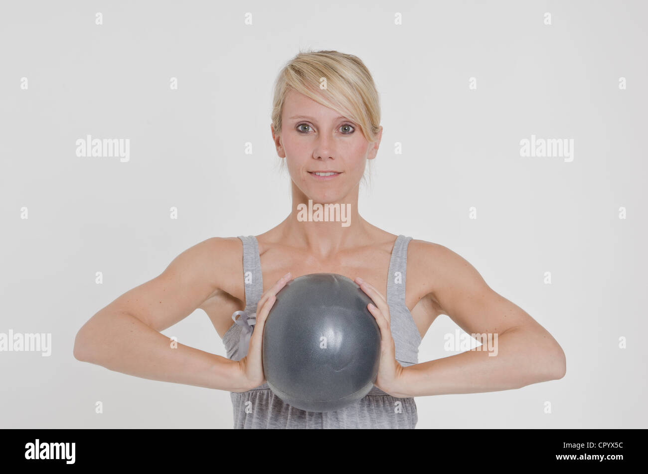 Young woman holding an exercise ball with both hands - Stock Image