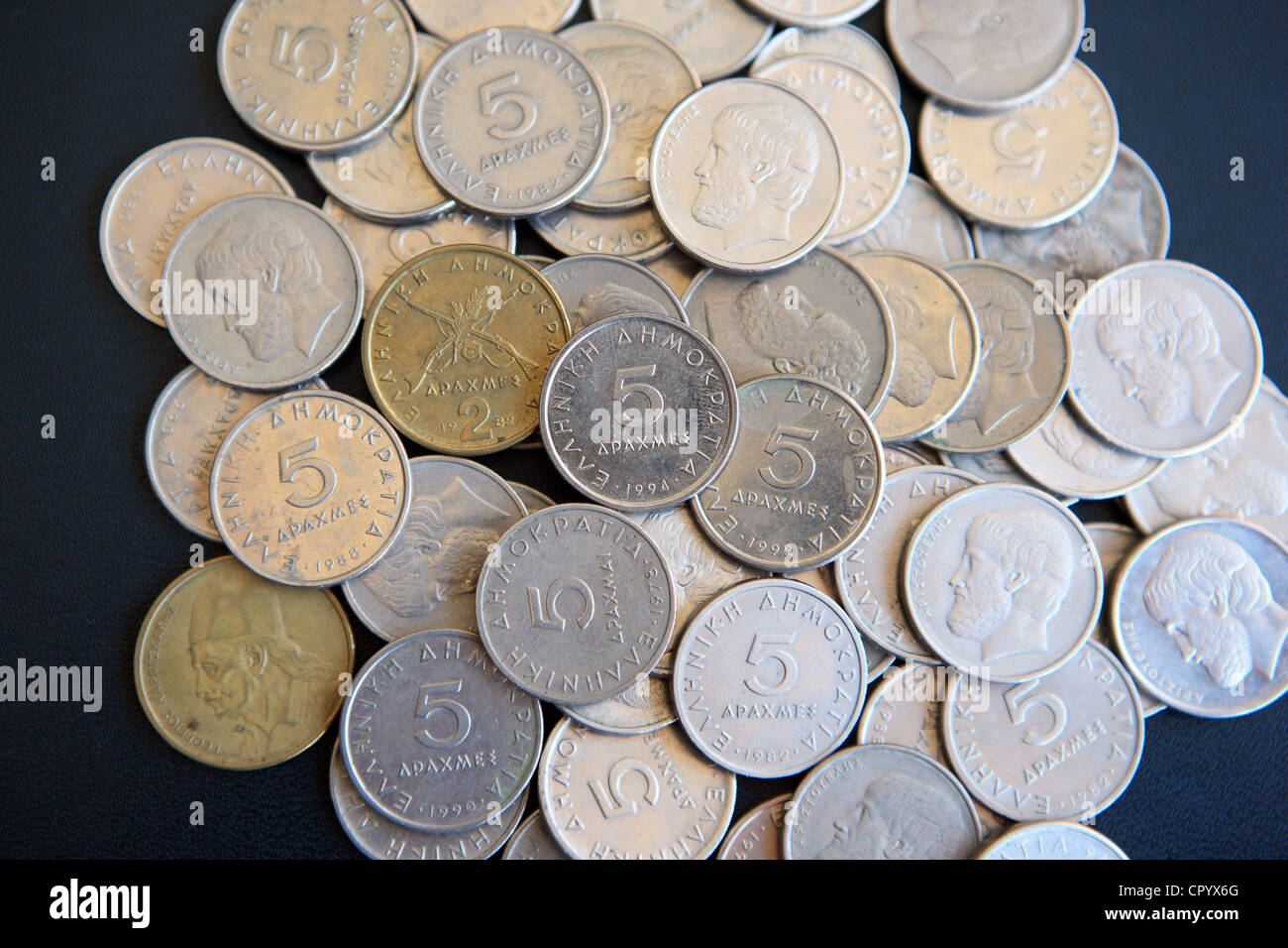 Pile of Greek Drachma coins on a black background - Stock Image