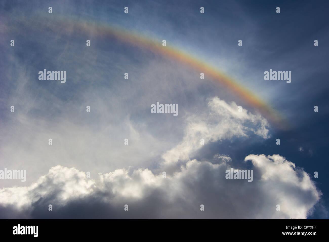 Rainbow against cloudy sky - Stock Image