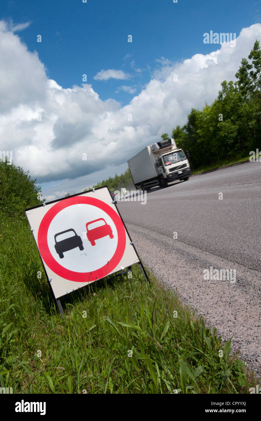 lorry passing no overtaking warning sign due to loose chippings on newly resurfaced road uk - Stock Image