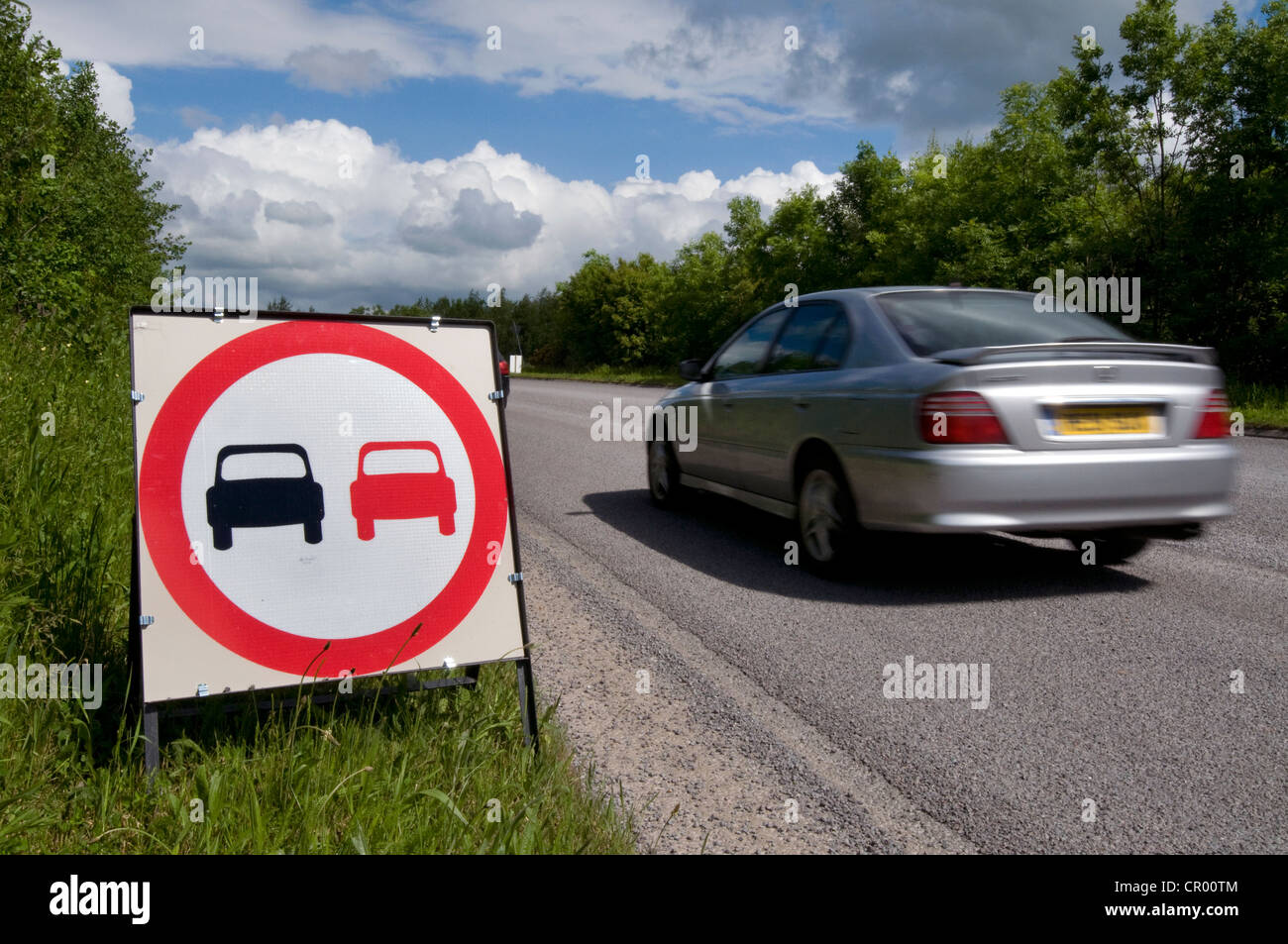 car passing no overtaking warning sign due to loose chippings on newly resurfaced road uk - Stock Image