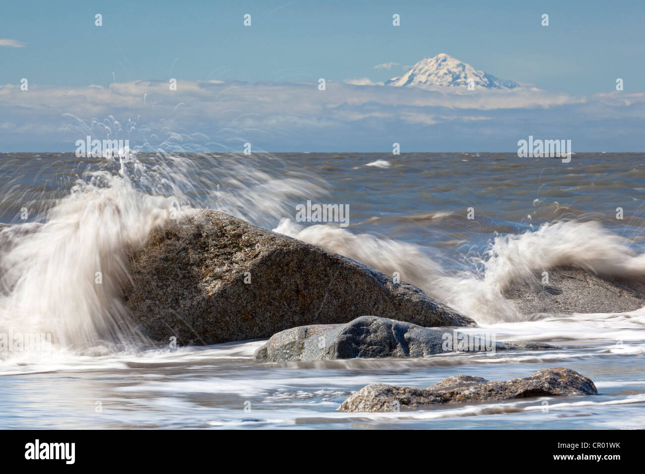Surf zone on the beach in Kenai on the Kenai Peninsula with Mount Redoubt volcano in the Cook Inlet, Alaska, USA - Stock Image
