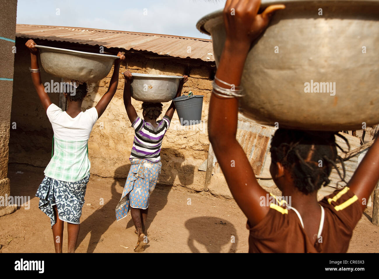 Girls carry water containers they filled from a communal well in the village of Kiendi-Walogo, Zanzan region, Cote - Stock Image