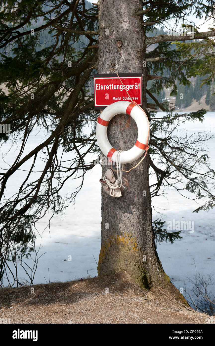 Life saver for breaking through the ice hanging on a tree, bank of the frozen Lake Spitzingsee, Bavarian Alps, Upper - Stock Image