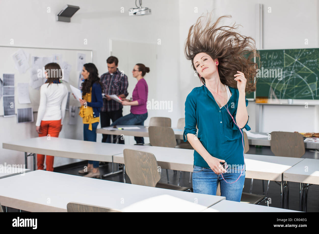 Student dancing to mp3 player in class - Stock Image