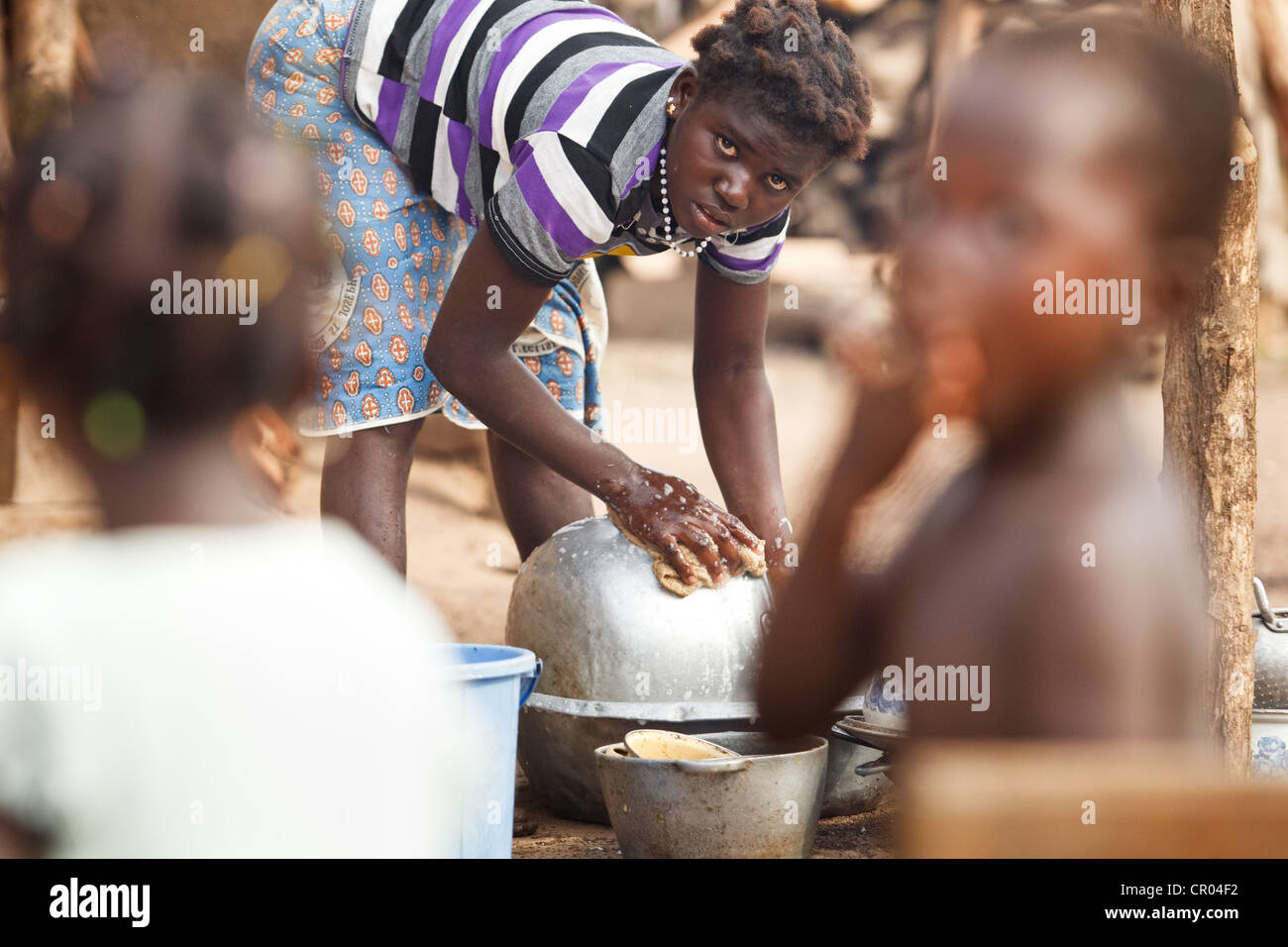 Afoua Clarisse, who doesn't know her age, cleans dishes outside her home in the village of Kiendi-Walogo, Zanzan - Stock Image