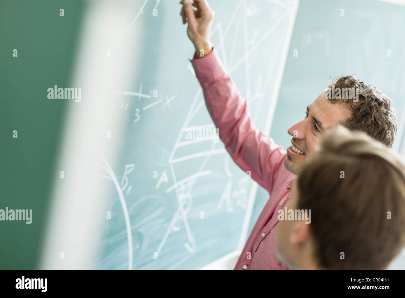 Teacher and student working at board - Stock Image