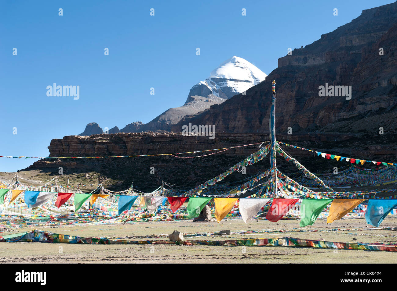 Tibetan Buddhism, Tarboche, a flagpole with colourful prayer flags, in front of the snow-covered holy Mount Kailash, - Stock Image