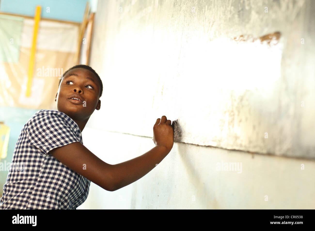A girl writes on the blackboard during class at the groupe scolaire Bondoukou Est primary school in Bondoukou, Zanzan - Stock Image