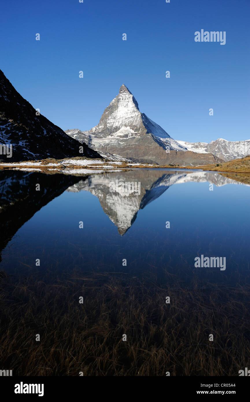 Matterhorn reflected in Lake Riffelsee, Zermatt, Valais, Switzerland, Europe - Stock Image