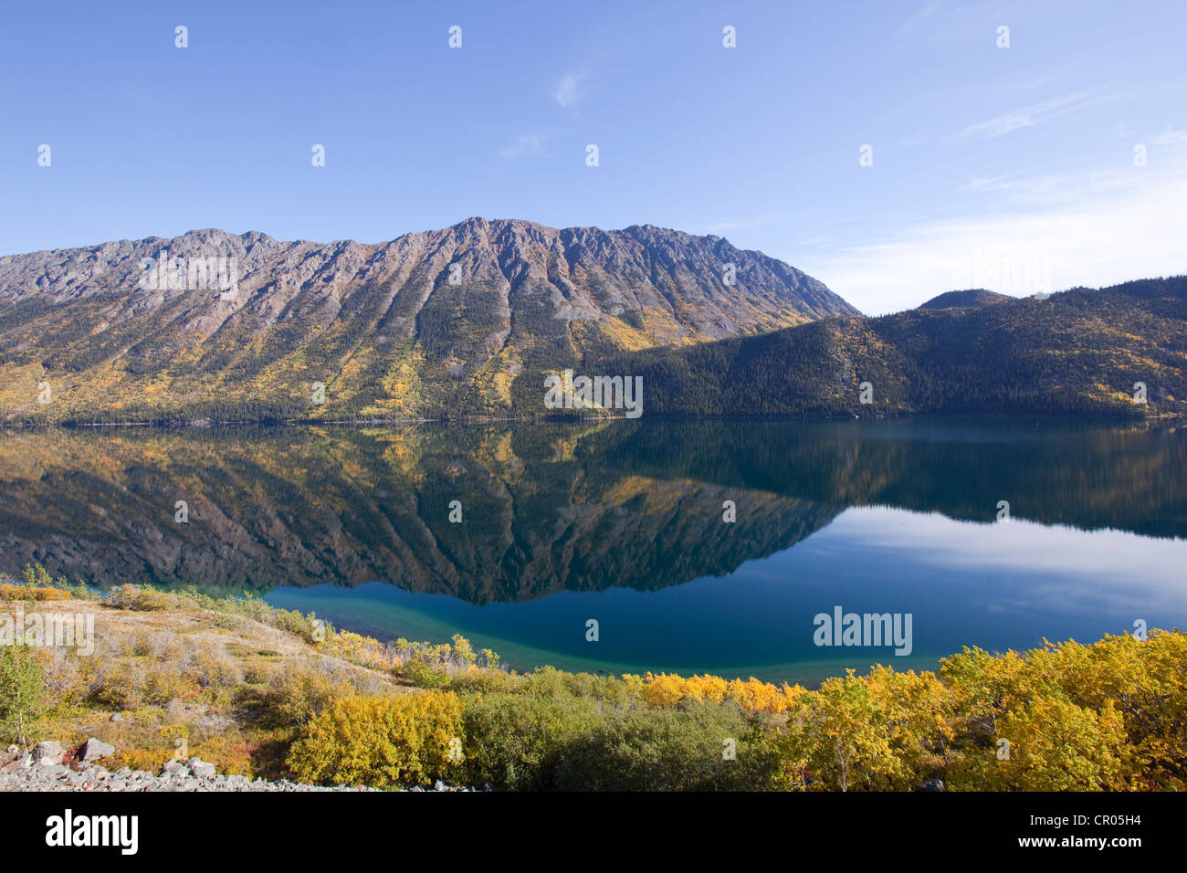 Calm windy arm of Tagish Lake, reflections, Escarment Mountain, Tagish Highland behind, autumn, Indian Summer - Stock Image