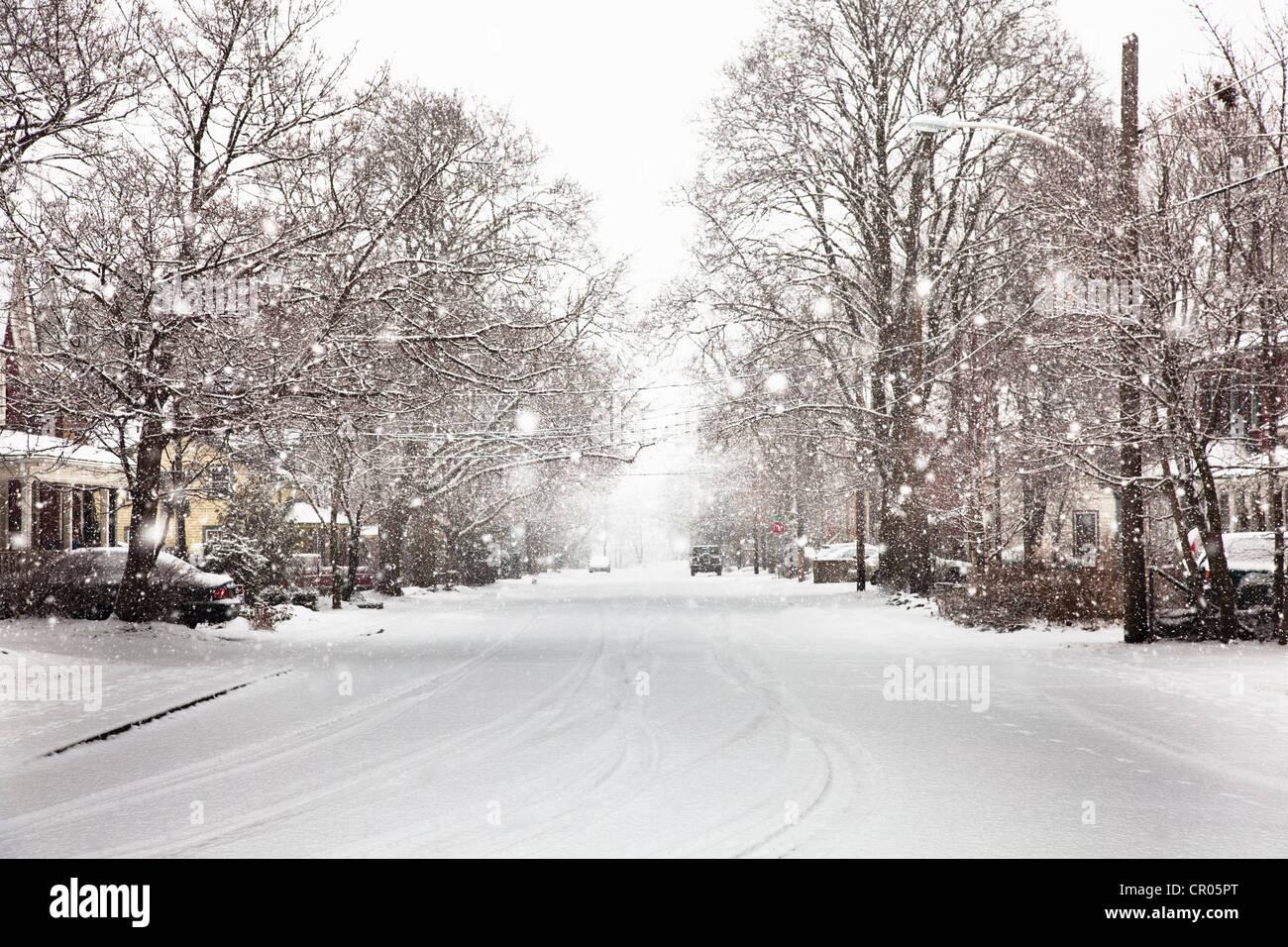 Snow falling on suburban street - Stock Image