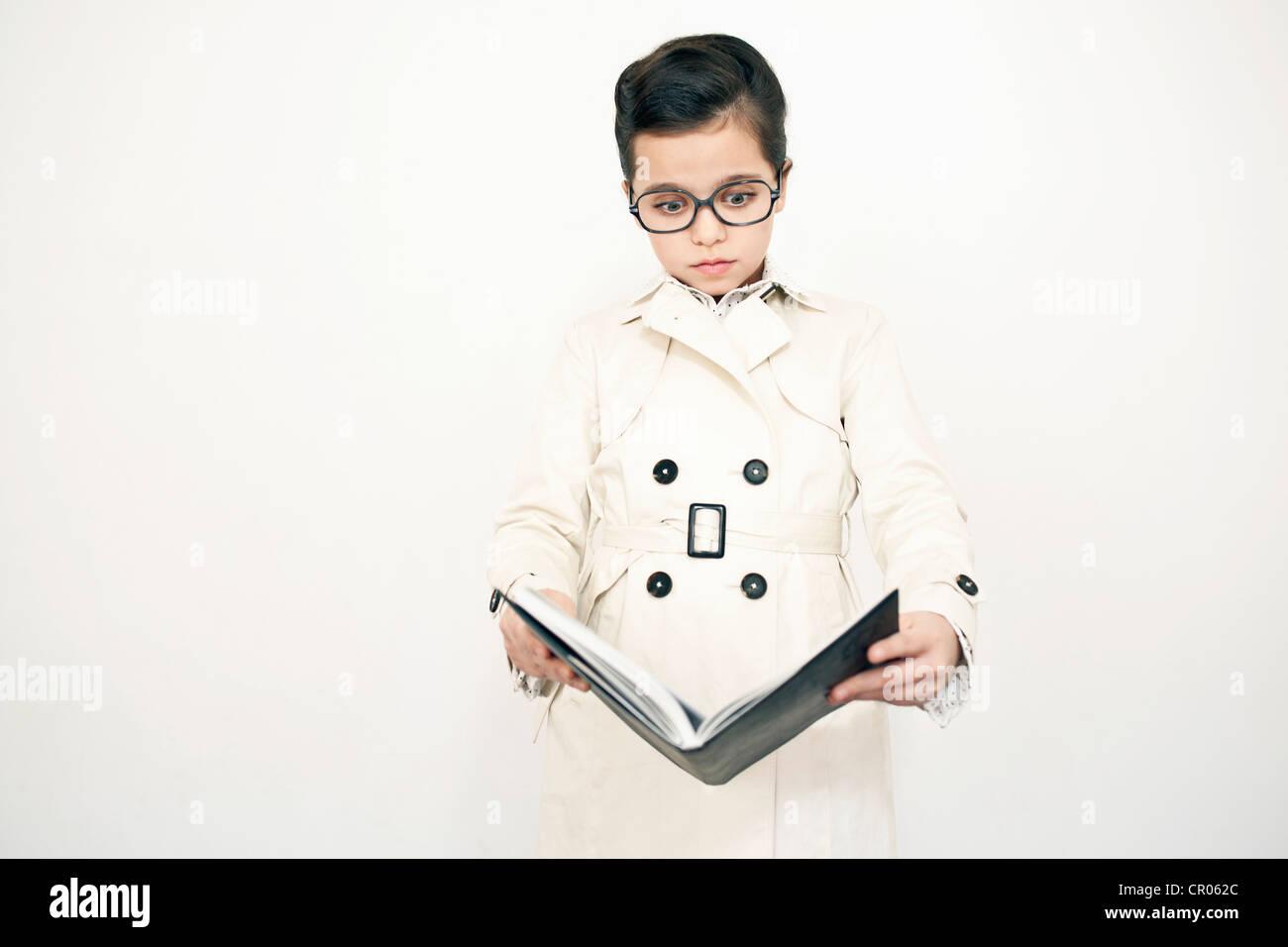 Girl in eyeglasses reading book - Stock Image