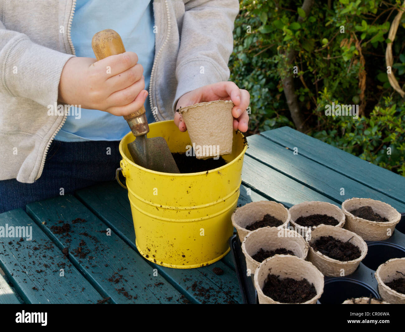 Child Filling Small Plant Pots With Compost To Plant Seeds Using A