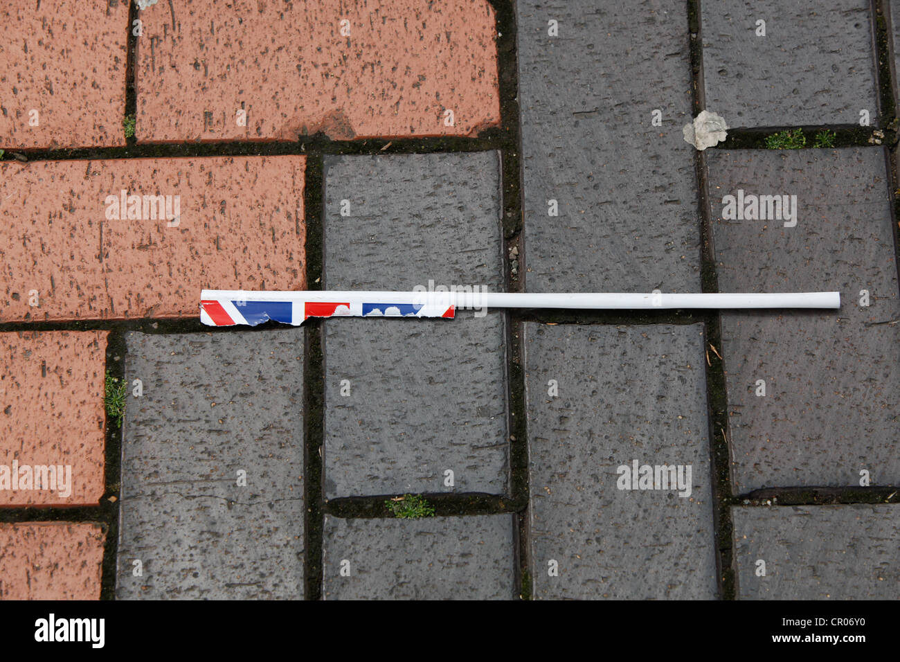 Remnants of a torn Union Jack flag discarded in block paved city center public area. - Stock Image