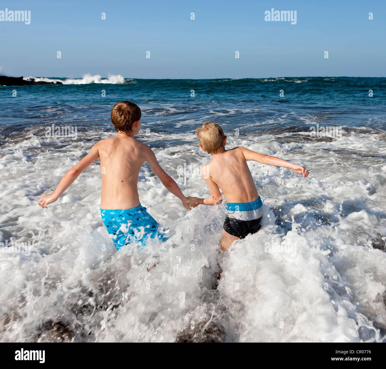 Children playing in the surf, Playa Jardin beach, Puerto de la Cruz, Tenerife, northern part, Canary Islands, Spain, - Stock Image