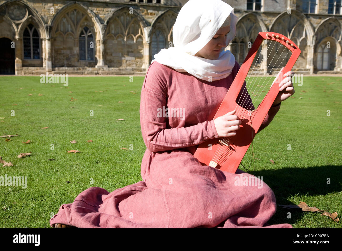UK. England. Battle Abbey. East Sussex. Woman in medieval costume seated outside on grass lawn. playing traditional - Stock Image