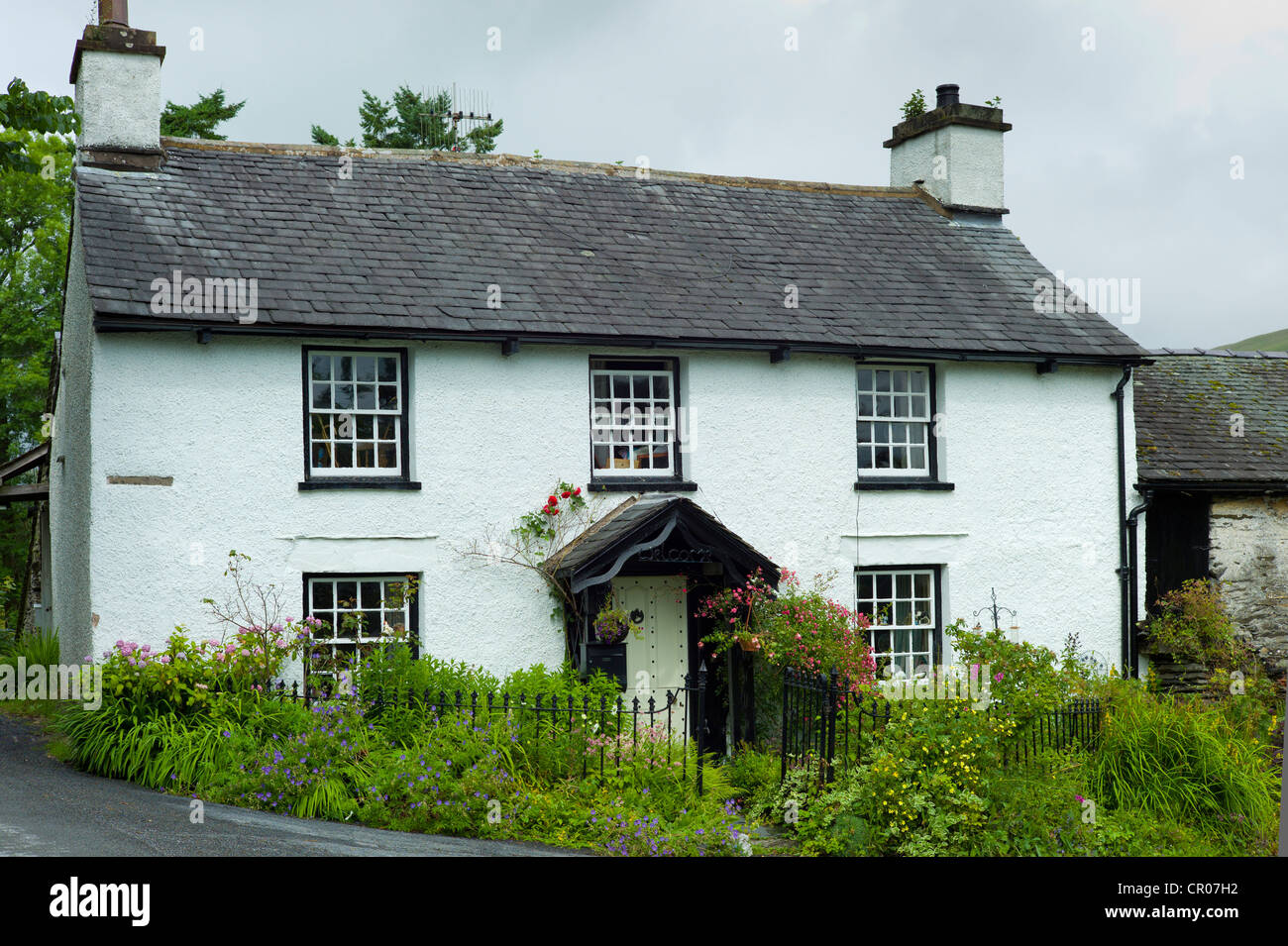 Quaint lakeland cottage and country lane at Troutbeck in the Lake District National Park, Cumbria, UK - Stock Image