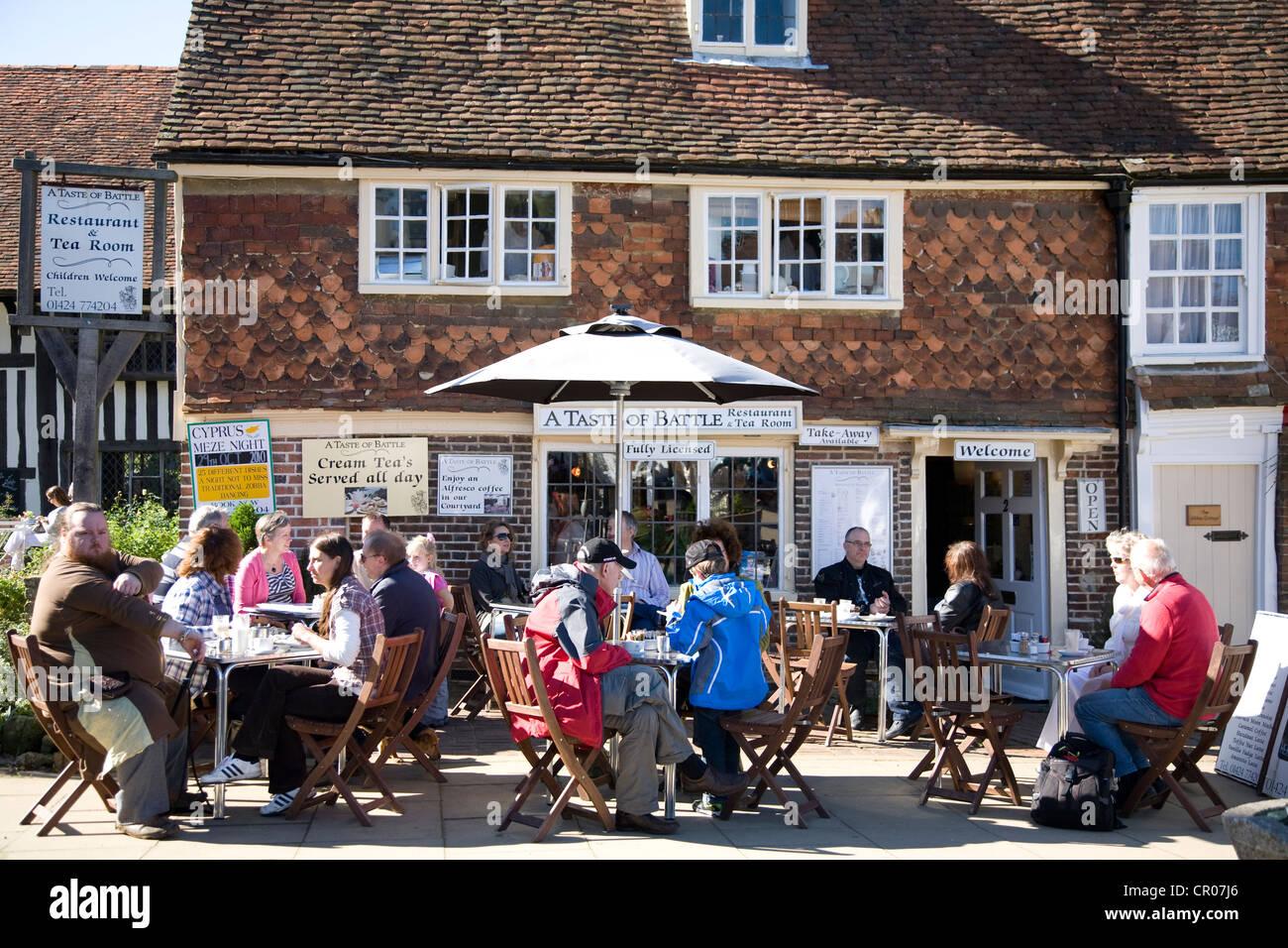 People seated outside Tea Room. High Street. Battle. East Sussex. England. - Stock Image