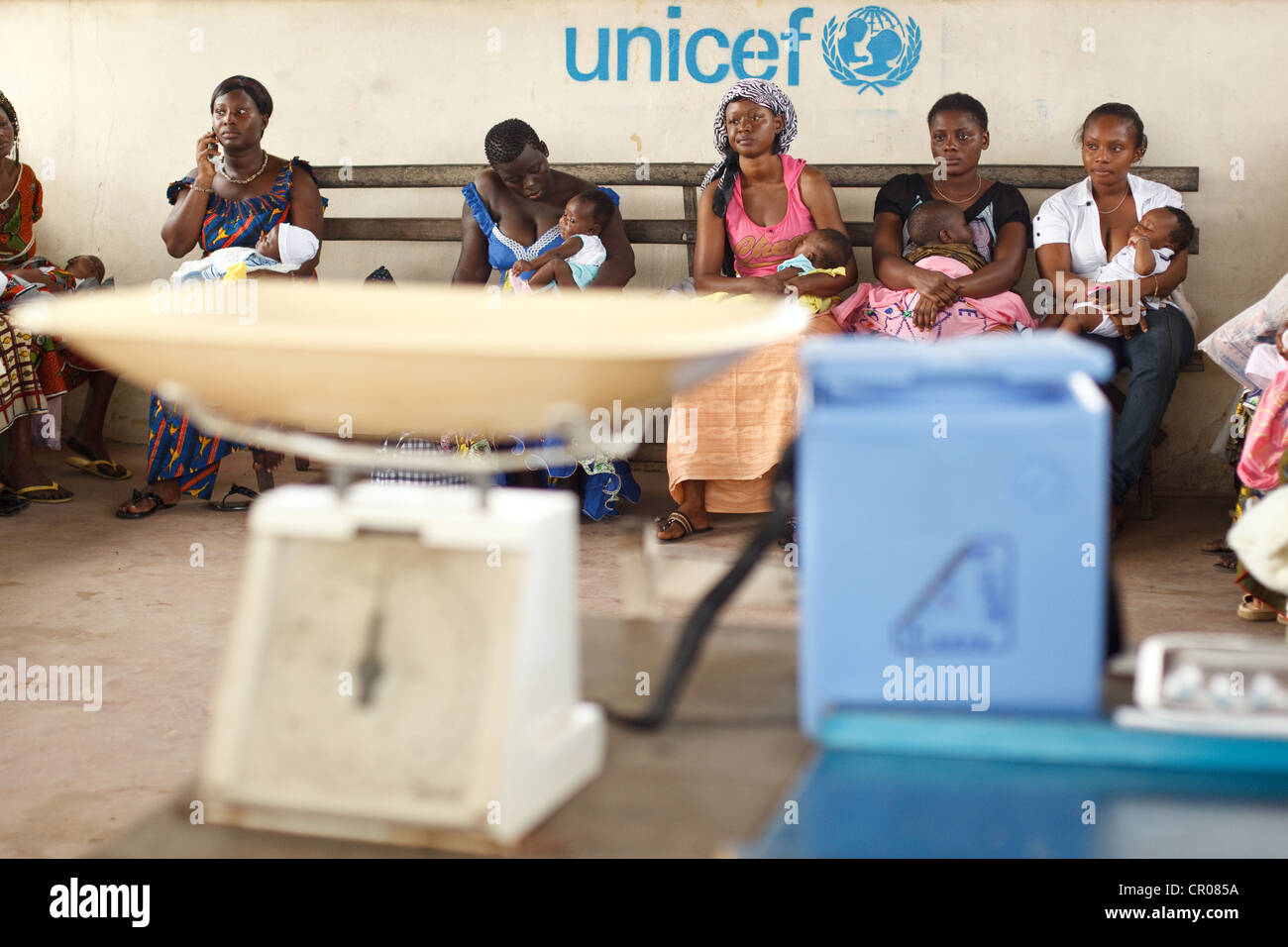 Women wait to have their children vaccinated during a routine follow-up visit at the Henriette Konan Bedie Community - Stock Image