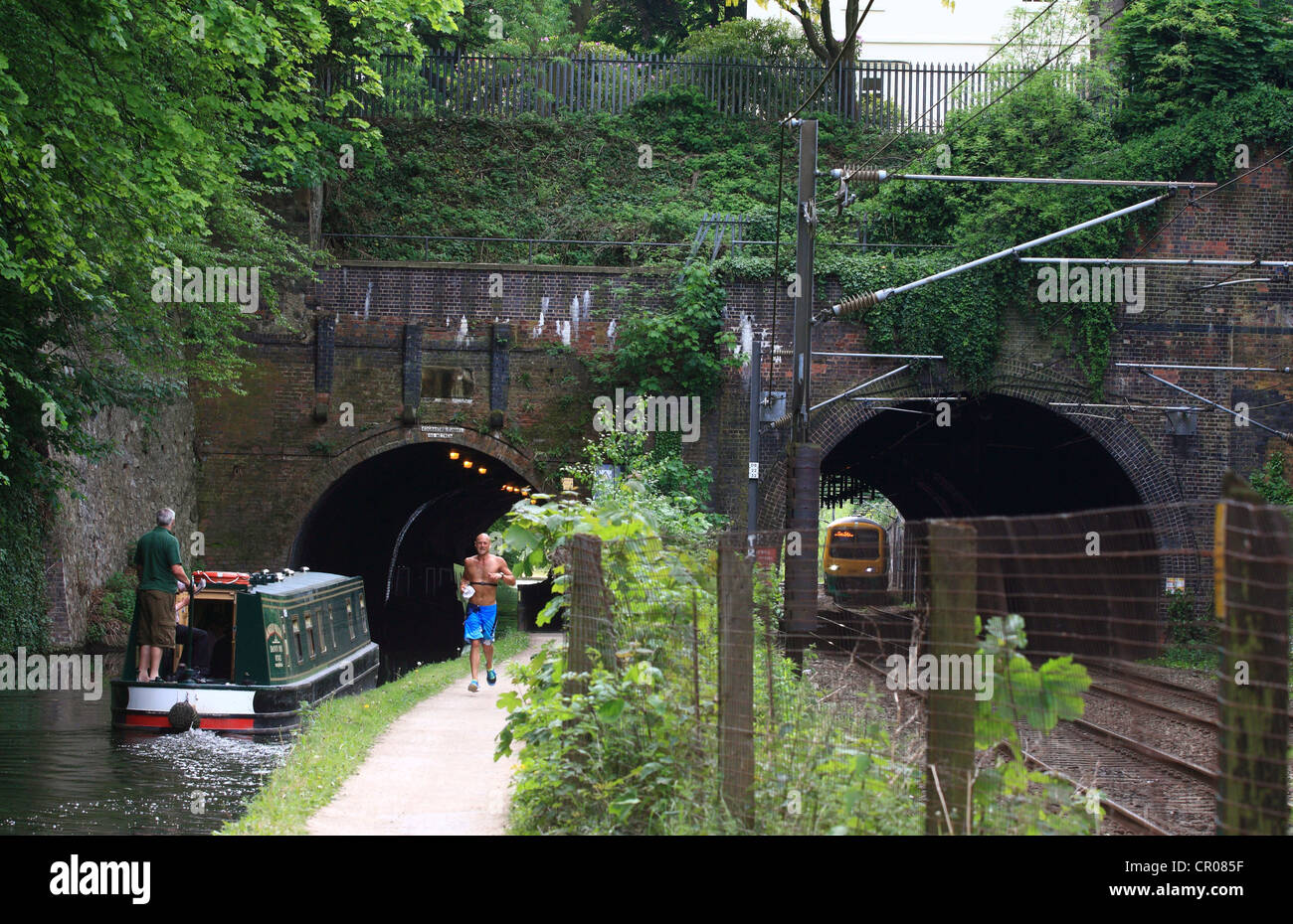 a view of a bridge with two arches - one crossing a railway and the other crossing a canal in Birmingham - a jogger Stock Photo