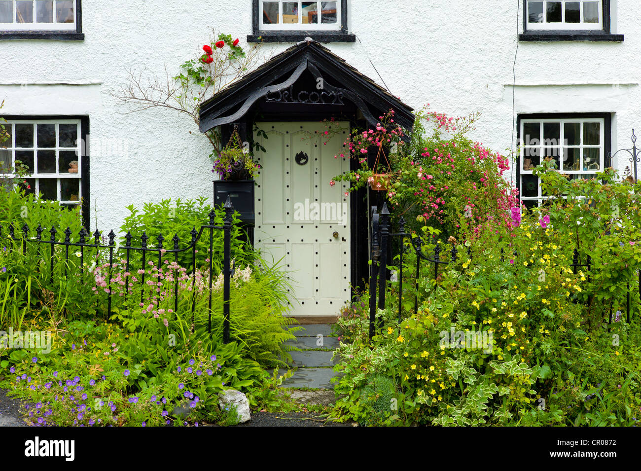 Quaint lakeland cottage with studded front door and Welcome sign, at Troutbeck in the Lake District National Park, - Stock Image