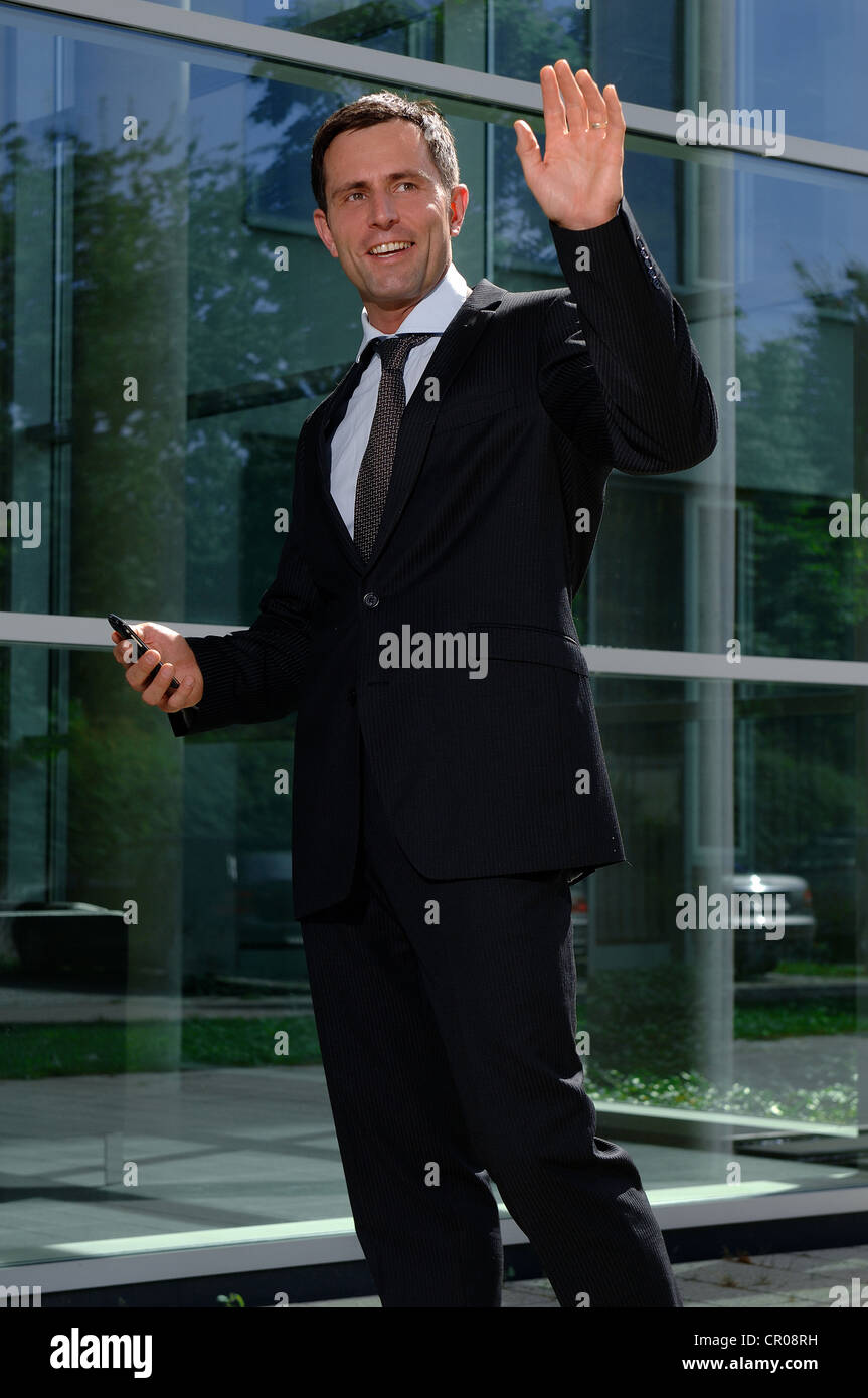 Business man greeting someone outside a bank - Stock Image