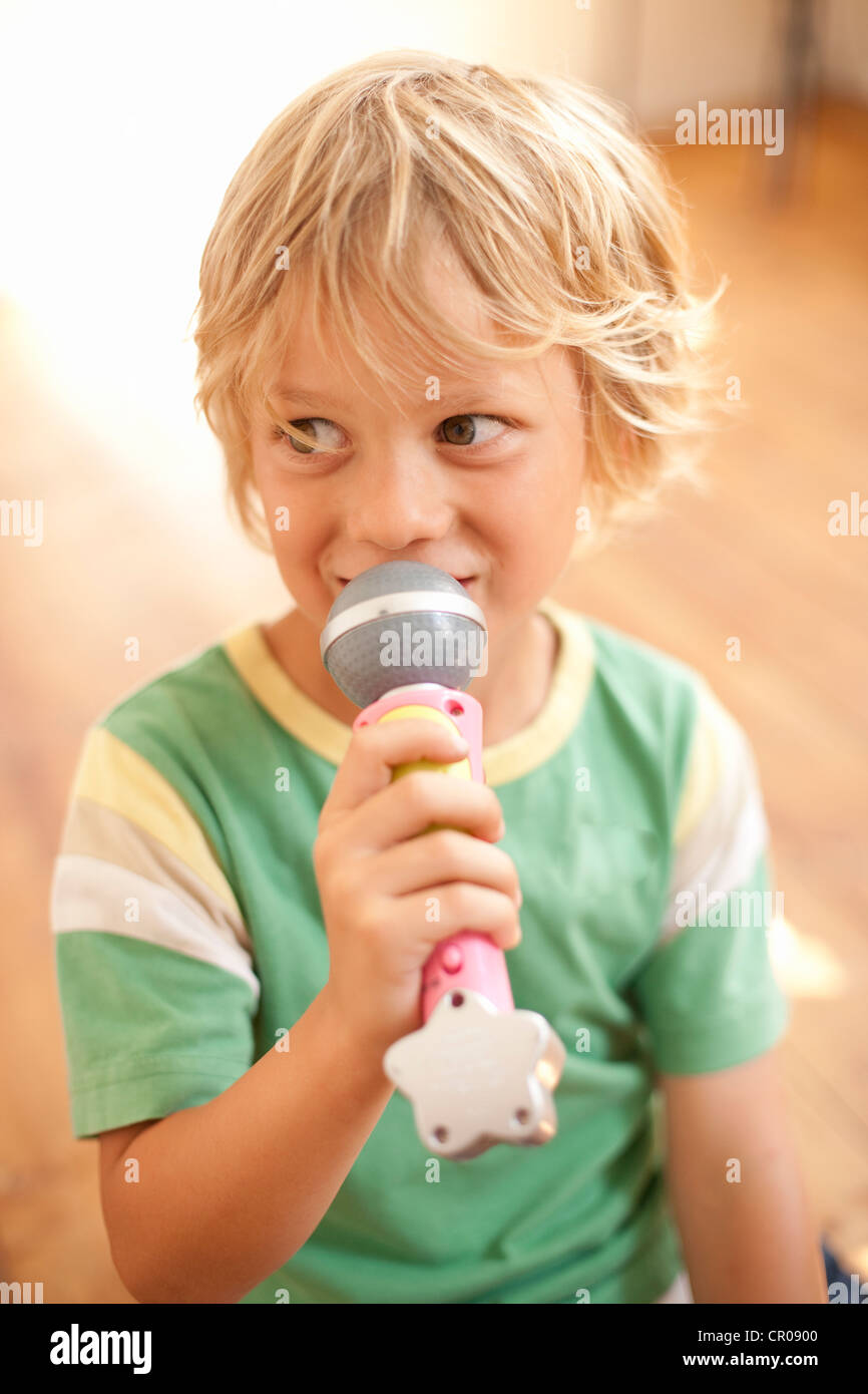 Smiling boy playing with toy microphone - Stock Image