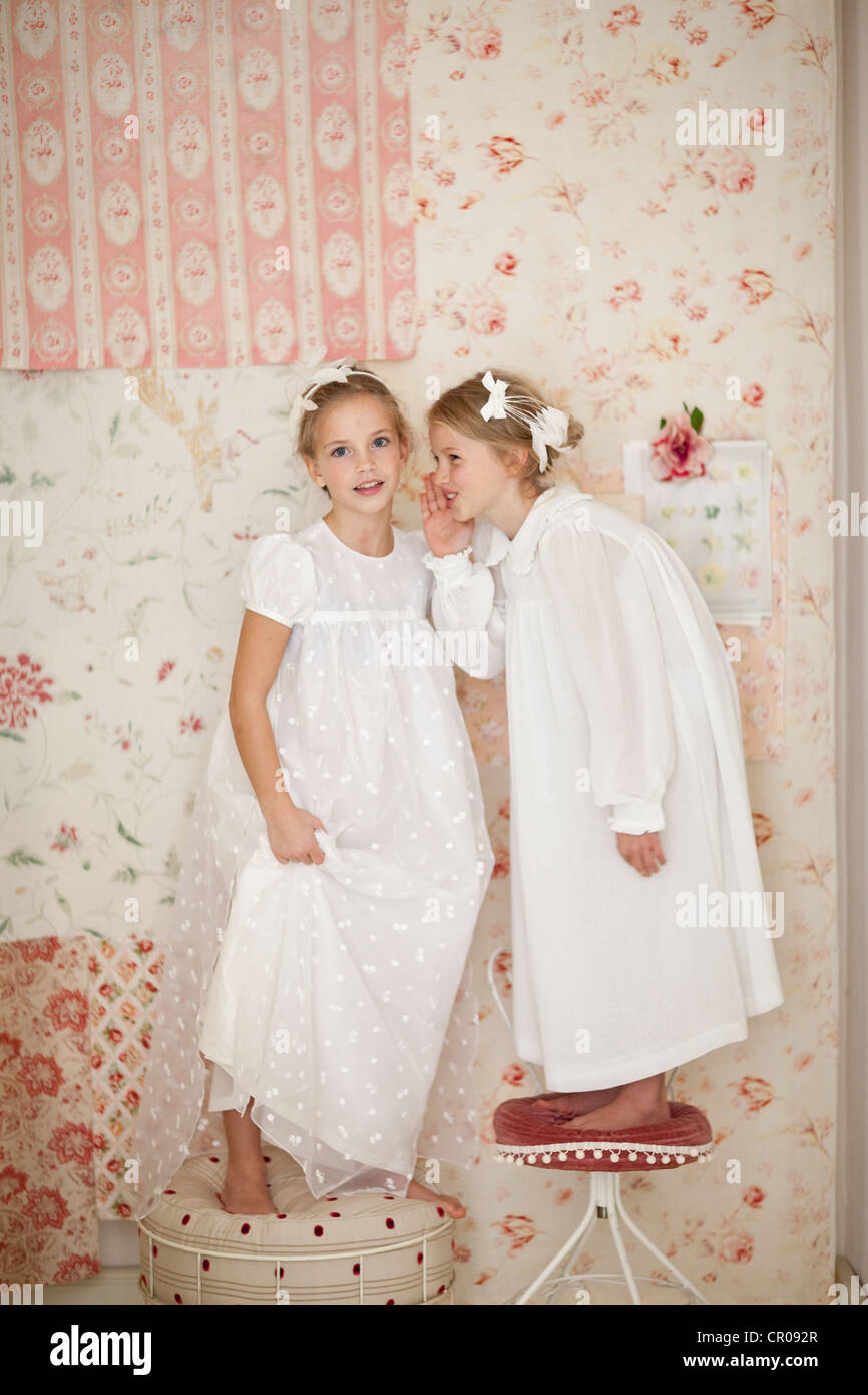 Smiling girls whispering together - Stock Image