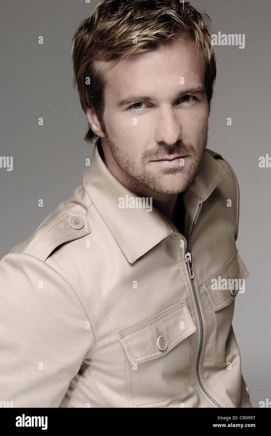 Man in his mid-thirties, beige shirt, portrait - Stock Image