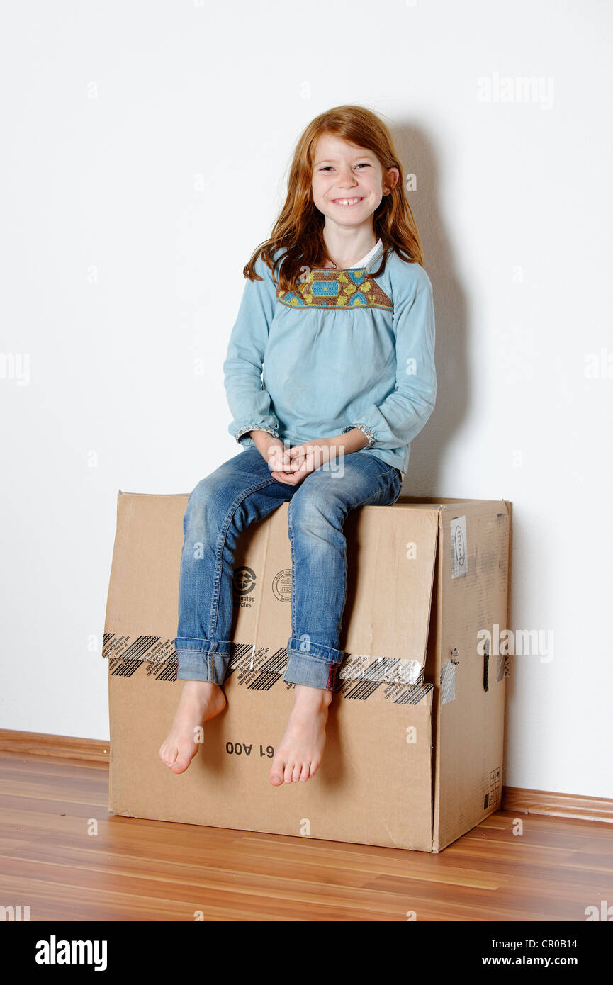 Girl sitting on a cardboard box, packing case - Stock Image