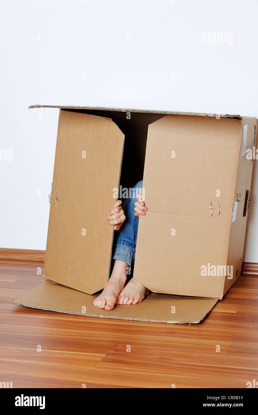 Girl hiding in an empty cardboard box - Stock Image