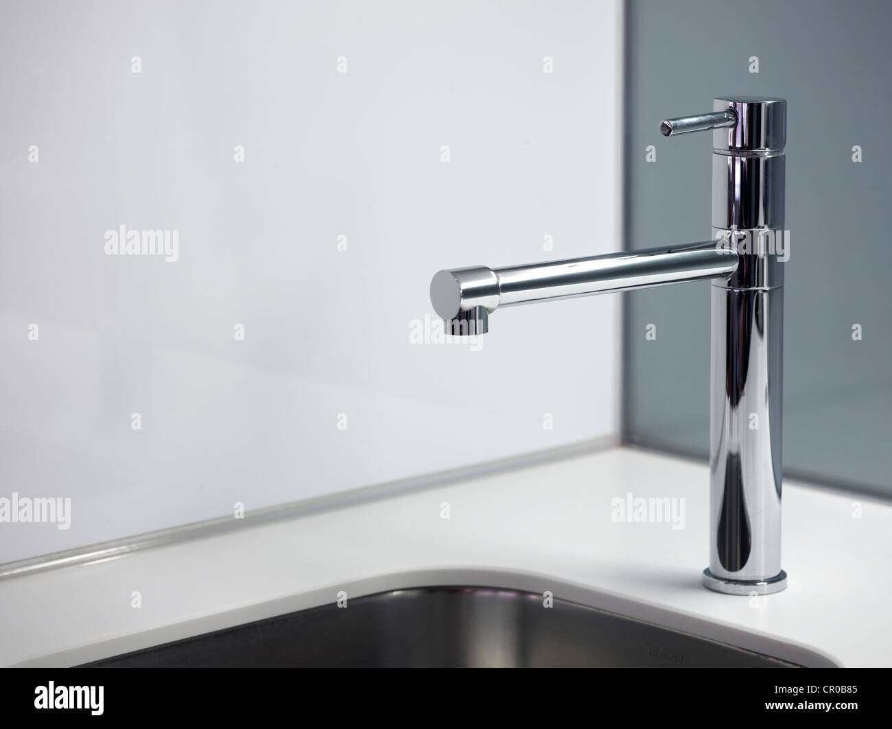 corner of minimalist modern designer kitchen with tap and sink in white and silver - Stock Image